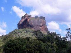 【シーギリヤ ロック(世界遺産)】  旅行3日目は、朝から、本ツアーのハイライト、世界遺産でもあるシーギリヤ ロックの観光に出発。  標高約370m、岩そのものの高さは約195m。 5世紀にカッサパ1世によって建造された、岩上の王宮跡。 一体全体なんでそんなところに王宮を…とお思いでしょうが、なんでも、このカサッパさん、クーデターを起こして父を殺して王権を奪取するんだけど、お母さんが一般庶民の出身。 このままじゃ、王族出身の母を持つ弟にいつか王位を奪われちゃうかも、とビビりまくり、首都であったアヌラーダプラを離れ、ここなら弟がせめてきても大丈夫だろうってことで、岩山の上に王宮を立てたんだって。  ま、結局、最終的には攻めてきた弟に負けて自害しちゃうんだけどね。 (なにこの韓流時代劇みたいなパターン(;^ω^))  その後、都は再びアヌラーダプラへ戻るので、こちらは徐々に衰退。 王亡き後は修道院として1世紀ほど存在していたらしいけど、その後16世紀ぐらいまでは記録すら残されていないんだって。いやでも、良かったよね、カッサパさんに感謝しないとね。 今や世界中からこれ見たさ、登りたさに観光客が来るんだもん。