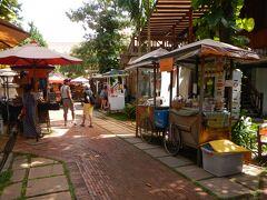 中庭の「メイドインカンボジアマーケット」 メイドインカンボジアにこだわるショップが屋台形式で並んでいます。  情報によればオープンは12:00~ ちょっと早めだったので準備中のお店もありました。  クロマー専門店でクロマーを購入したり クメール文字のペンダントヘッド(銃弾からつくったとのこと) を購入しました。