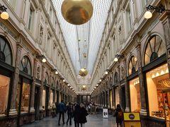 続いて「ギャルリ・サンテュベール」へ来ました。 ヨーロッパ最古の高級ショッピングアーケード。 1847年の設計でガラス張りの屋根のもと、 デザイナー、皮革製品の職人、宝石商なども住み着き、 レースやタペストリー、チョコレート、家具や内装など エレガントなお店が軒を連ねています。