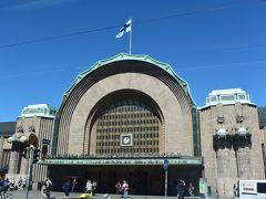 ヘルシンキ中央駅の前を通りました。  中央駅正面にはランプを持った4体の像が立っています。 駅舎はフィンランド産の花こう岩で作られているそうです。 (写真は後日、昼間に撮影)