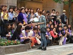 宝塚劇場前で出待ちをしていた人々。 おそろいの紫のスカーフをしている人たちが、このスターのファン。ファンの前で立ち止まっておしゃべりや握手をするようです。 後ろに立って写真を撮っているのは一般人。
