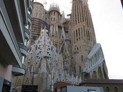 建物の間から、サグラダ・ファミリア(Sagrada Família)の受難のファザードが見えました。 サグラダ・ファミリアは日本語で「聖家族贖罪教会」と呼ばれ、アントニオ・ガウディがライフワークとして設計・建築に取り組んだ教会です。 着工当時約300年かかると言われていた工期は、技術や工法の進歩によって半分ほどに短縮され、ガウディ没後100年の2026年に完成予定です。