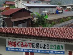 駅の側の建物に掲出された横断幕。   「地域ぐるみで応援しよう三江線!!」・・・もう一年もしないで廃止だけどな。廃止が決定する前から掲出してるんだろうか。