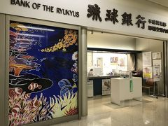 向かい風の影響とかで、更に予定より遅れて15:40くらいに那覇空港に到着!  スーツケースは持ち込んでいたのですぐに出られました。  次の飛行機まではまだ時間があるので、まずは沖縄料理を頂きましょう♪  お目当てのお店は到着ロビー1階の右奥にある空港食堂。  あっ、琉球銀行! この美しい海の中の絵は、以前、琉球銀行主催の「りゅうぎん紅型デザインコンテスト」に入選した私の友達の作品なのです(^o^)