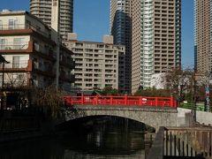 まだお腹が空いていないので先に住吉神社を目指します。 赤い橋は佃小橋です。 日の出湯という銭湯の煙突があります。