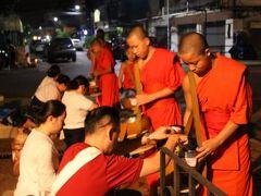 敬虔な信者の方々が次々と来る僧侶の丸い器にご飯やお菓子を入れて功徳積みます。