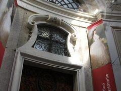 シシィにちょうど光が射し込んで、まるでスポットライトを浴びているみたい。  以前はこの入口にシシィのシルエットが飾られていたのに、今はなくなってしまったようです。  では、早速見学しましょう。 ちょっと出遅れてしまったけど、シシィ・チケットをネットで購入していたのですぐに入れました。  シシィ・チケットとは、旧王宮とシェーンブルン宮殿、王宮家具博物館に入れるコンビネーションチケット。 チケットを買うために並ばなくて良いのと、シェーンブルン宮殿は通常日時指定が必要なところ、このチケットがあればいつでも入れるので大変お得なのです。 チケットの有効期限も1年なので、無理に1日で回る必要もありません。  旧王宮とシェーンブルン宮殿だけだと気持~ち元が取れないのですが、並ぶ時間を考えたら良いかと。 私たちは王宮家具博物館にも行く予定だったので、しっかり元は取りました。  ★Sisi Ticket 予約ページ(ドイツ語・英語) https://www.imperial-austria.at/sisi-ticket.html 大人 ひとり  29.9ユーロ  (2019年5月現在、34ユーロに値上げしています)  こちらの「旧王宮」ですが、宮廷銀器コレクション・シシィミュージアム・皇帝の部屋と、旧王宮内にある3つの博物館から成り立っています。  ちなみに、シシィはエリザベートの愛称です。