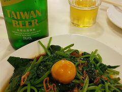 鶏肉大好きな私は、いつかこのお店で食べたいと思ってたので、結果オーライ。 お客さんの半分以上は日本人で、駐在員とおぼしき男性グループや家族連れなどが賑やかに食事を楽しんでいました。 トイレがきれいなのと、ビールが冷えてるのが日本人には嬉しい…人気なのも納得です。  写真は、冷えた台湾生ビールと青菜炒め。これが美味しくて最高!ちなみにてっぺんの丸いのは醤油漬けのニンニクでした…。 青菜は、台湾ではポピュラーなサツマイモの葉っぱ。少しぬるっとした食感がヤミツキ…今後は空芯菜よりもこっちが定番になりそう。子どもたちもパクパク食べ、なくなると「もっとないの~?」と言うほど気に入っていました。