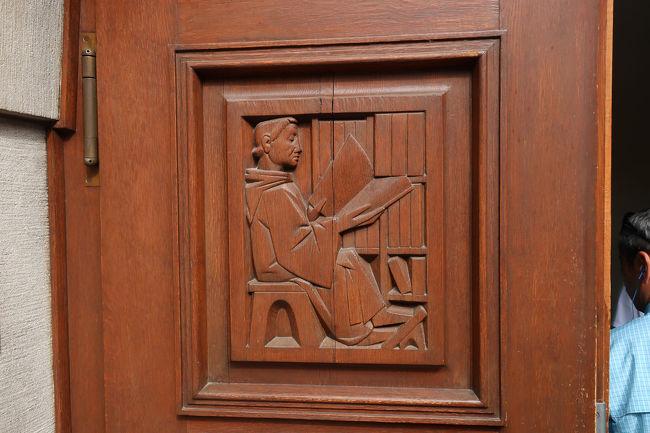 修道院入り口の木製扉。本を読んでいる姿のようなレリーフが印象的