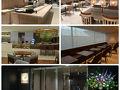 今回の楽しみはJALのファーストクラスラウンジ。 5月に成田国際空港第二旅客ターミナル本館4階を改修してオープンしたラウンジです。 入ったらお寿司カウンターがありテーブルが並びます。 こちらは白木を使った和モダンのスペース。 奥に進むとオーダーするカウンターがあるダイニング。