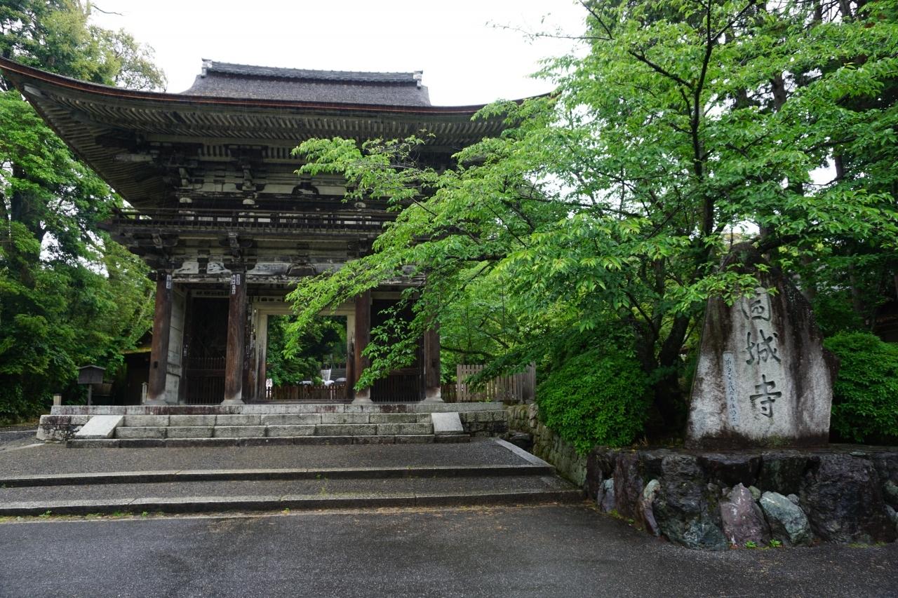 """園城寺(三井寺)  大友皇子の息子、""""与多王""""が父の霊を弔うために創建されたのがはじまりと言われています。 その後平安時代になってから、智証大師円珍和尚が現在の形に整えられたとのこと。  正式名称は園城寺ですが、天智・天武・持統天皇と、三天皇の産湯に使われた霊泉が沸いていたことから三井寺と呼ばれるようになったそうです。  入口横には立派な山門。 仁王像が両脇でお寺を守っていらっしゃいます。"""