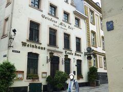 """かつて会社の部下たちと訪れた*アンナ小母さんのレストランWeinhaus Tante Annaワインハウス・タンテ・アンナの店の横丁を通り、ライン川畔プロムナードに行ってみる。  写真は懐かしのデュッセルドルフ旧市街:Weinhaus Tante Annaワインハウス・タンテ・アンナ前で  *2006年に夕食を食べたアンナ小母さんのレストランは20世紀初め、人気者の女将に因んで、名前を""""アンナ小母さんのワインハウス"""" としたそうだ。古くは1593年、イエズス会修道院の礼拝堂として、建造されたと云う。店内には1000年の歴史を感じさせる黒く古びた花崗岩の柱がみられ、300年の年月を経たアンティークの家具で飾られた、落ち着いた雰囲気をもつ家庭的料理とワインの店です。"""