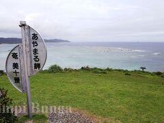 あやまる岬の看板。 空が曇っているせいもあり、期待していた海の色が…