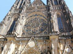 第三の中庭に入ると他を圧倒するような建造物が聳え建っていました。 これが聖ヴィート大聖堂です。建物が大きすぎて、塔も高すぎて聖堂のファザードは写真のファインダーに収まりません。本当にどでかい建物です。 聖ヴィート大聖堂の正式名称は「聖ヴィート、聖ヴァーツラフ、聖ヴォイテフ大聖堂」で3人の聖人の名前を冠したプラハ大司教の司教座聖堂です。 925年、ボヘミア公国のヴァーツラフ1世によりロマネスク様式の教会として建てられましたが、1344年ボヘミア王カレル1世兼神聖ローマ皇帝カレル4世の命によりゴシック様式による改築が始められました。 しかし、フス戦争による建設の中断やフス派の聖像破壊運動による内装の破壊、資金不足による中断、1561年の大火など紆余曲折を経て完成したのは20世紀になってからでした。実に完成まで600年の歳月を要しました。 この大聖堂は奥行き124m、幅60m、ファザードの塔の高さは82m、中央の塔の高さは99mあり、内部は見事なステンドグラスで飾られています。 聖ヴィート大聖堂は後期ゴシック様式の発展に大きな影響を及ばしました。ウィーンのシュテファン大聖堂やストラスブール大聖堂など中欧の多くの教会の建築に影響を与えました。 大聖堂の入り口は西側、ファザードの上部には大きなバラ窓があります。