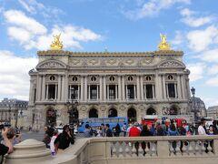 【8/9】 2時頃までヴェルサイユ宮殿に滞在した後、ヴェルサイユ・リヴ・ゴーシュ駅から地下鉄PERに乗ってパリに戻ってきた。 オペラ駅に3時過ぎに到着。地上に上がるとすぐにオペラ座だ。 外観を眺めるだけでも、その堂々たる美しさに感動できる。 この写真ではチラッとしか見えないが、屋根の頂点に、堅琴を高々と掲げる音楽の神「アポロン」の銅像がある。 この堅琴はこのオペラ座のシンボルだそうです。  屋根の両脇の黄金に輝く像は、左側がハーモニー、右側がポエジーの女神。  パリにはオペラ座が2つあり、最も有名な9区のこのオペラ座は「パレ(オペラ)・ガルニエ」と呼ばれている。 日本人はガルニエ宮と呼ぶことが多いので、ここではガルニエ宮と表示します。 (ガルニエとは設計者の名前) あと1つは12区のバステューユにある、オペラ・バステューユ。 ガルニエ宮では、主にバレエ、小規模オペラ、管弦楽コンサートが行われており、 オペラ・バステューユは1989年に完成した新しいオペラ座で、大規模オペラが中心とのこと。 1日目の街歩きの時に外観のみ見ましたが、 近代的な大きな建物でした。  ホテルがこのパレ・ガルニエの近くなので毎日そばを通過していたが、今日はいよいよ中に入ります。 入場は4時半までなので、セーフ!