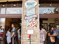 "Lunchをしにやってきました。地下鉄のA線Cipro駅が最寄駅  ""せっかくなので、ピザ""と思いましたが、レストランに行くと、一人では食べれないくらい、大きい可能性大と思い、量り売りのピザ屋さんへ  中央に、番号札を取る機械があります。まず番号札をとって、自分の番を待ちます。私が行った時は10人ちょっと前にいましたが、中で2~3人の店員さんが対応してるので、そうは待ちませんでした。番号を呼ばれるまでに、人をかき分けて中に入って、自分が食べたいものの目星をつけます。"