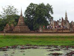 池を挟んで遺跡が見えた。  『マハタート遺跡』。  200m四方の堀に囲まれた、王宮を兼ねる寺院で、  18の聖堂と185基の仏塔が集まる、スコータイ最大の遺跡だ。