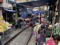 メークローン マーケット (折りたたみ市場)   『タイ国政府観光庁公式サイト』によると… 線路の両脇に野菜や果物などのお店が所狭しとひしめき合うメークローン駅近くの市場。別名タラート・ロムフッブ=傘をたたむ市場。その名の通り、線路脇で商売をする人たちは、メークローンとバーンレーム間を往来する列車が行き交う時に、店のテントや傘をたたんで列車を除け、列車が過ぎ去れば再び傘やテントを広げて商売を再開します。売られている物は、メークローン名物のプラートゥ(あじのような魚)のほか、果物、カレーペースト、日用品など庶民の生活を支えるまさに台所です。列車が通過する度に店をたたむようになったのは1984年頃からと言われ、世にも珍しいこの光景は、一見の価値あり。