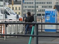 公営交通に乗るときは、カードの裏のバーコードを機械にタッチします。  写真中央、タッチしている人が見えますね。右は自動販売機です。ヘルシンキカードは自動販売機では買えません。