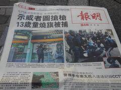 【前日の事件を伝える「明報」】 22日、対岸には高層ビル群を望む、尖沙咀のビクトリア・ハーバーで香港紙を読む優雅な朝。「明報」は香港で信頼されている中道リベラル系新聞。これによると、21日の屯門駅と元朗駅の抗議活動でも衝突があったらしい。13歳の子供が中国国旗を燃やして逮捕されたなど。 ちなみに、前日にはそのデモの情報があったので、行ってみようとも考えていたが、地下鉄が閉鎖されたので断念。