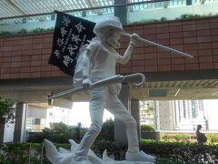 【完成度が高いデモ隊の像@香港大学】 「自由」な場所といえば大学。香港大学には抗議活動の後が保存状態よく残っている。 例えば・・・ デモ隊の像。右手には民主化運動のシンボルの雨傘を持ち、左手には「光復香港 時代革命」というスローガンが書かれた旗を持つ。かなり大きい。誰が造ったのか学生に聞いてみたが、知らないそうだ。
