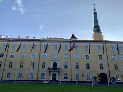 18:54国旗が掲揚されている立派な黄色い宮殿のような建物が。広場は『ピルス広場』、建物は『リーガ城』