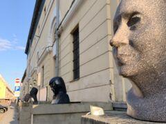 19:04トゥァルニャ通り、『アルセナール展示ホール』前の、顔の像の前を通って。偉人達の顔が並びます。