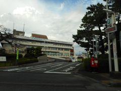 先日の東日本大地震で発生した津波の高さと被害の多さから、同じような中部大地震の発生が近く予定されており、津波被害から逃れる要件から、迅速に移転する為、広い駐車場を備えた高台に庁舎を建てる時間的地理的余裕がなく、一寸古いが耐震基準をクリア―している地震に強い建物を購入し、リフォーム工事で市役所として使用すべく、紀伊田辺駅近くの高台に移動する紀伊田辺市役所です。