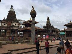 古い方のクリシュナ寺院 (1637年創建) Krishna Mandir はダルバール広場の北側にある四角形の寺院です。 写真の石柱の右の建物です。 2015年の地震では倒壊を免れたということです。