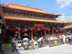 黄大仙廟(本殿)(道教の寺院です。)(中央の赤い丸に道教の三大理念である「師」「道」「教」の文字が書かれています。それぞれの線香台に三本ずつお線香を立てます。)
