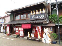 豊川稲荷表参道の店「いっぷく亭」  店の前だけでなく看板の上にもきつねが並びます。