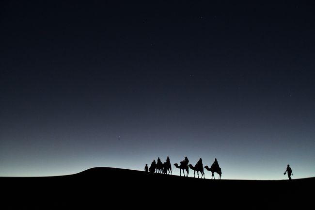 さて、まだ暗い砂漠をラクダに乗って日の出ポイントまで向かいます!<br /><br />私はラクダの姿を撮りたいので、ラクダに乗っていては撮れません。<br />だから砂丘を必死に登ったり降りたり・・・<br /><br />ただ、サハラ砂漠は勝手に入ることはできませんので、歩く私にもベルベル人ガイドがつきます。