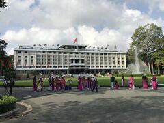 最初にホーチミン市内観光に行ったのは、統一会堂(旧大統領官邸)で庭園前には、赤いアオザイの団体が居ました。いいねえ。