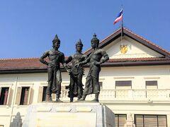 写真はチェンマイ市芸術文化センター前にある「3人の王像」です。 チェンマイ建国に所縁があるのがこの3人の王です。中央はラーンナー・タイ王国のメンラーイ王、右はスコータイ王国のラームカムヘーン王、左がパヤオ王国のカムムアン王です。 ラーンナー・タイ王国の首都はもともとチェンライでしたが、メンラーイ王はチェンマイに遷都しました。この時メンラーイ王は2人の王を呼び寄せチェンマイの町づくりを協議しました。 こうして建設されたのがチェンマイの旧市街ですが、この像はチェンマイの町の建設を誓い合っている様子を表しています。