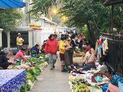 托鉢体験の後は、その近くの朝市を見学に。  こんな感じで、狭い路地で朝市が開催されている。 お供え物(右手前の緑の三角に橙の花)も売っていた。  狭いのに、レンタサイクルを押して進入してくる観光客がいて、 非常に迷惑だった。