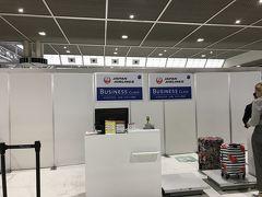 成田空港のJALビジネスクラスのチェックインカウンター。仮設です。なんで? 普通はベルトコンベヤーで運ばれていく預入荷物、スタッフがゴロゴロ転がして奥に持っていきました。