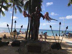 """ワイキキビーチのマストスポット デューク・カハナモク像 ハワイ出身の代表的なスイマーであり、サーフィン普及に努めた """"近代サーフィンの父""""です。 クヒオビーチとサーフボードを背にした彼の銅像には いつも沢山のレイが掛けられています。"""