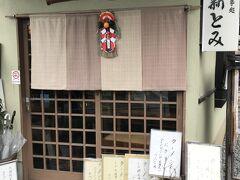 歩くこと数分。東慶寺を通り越してすぐのところに、この「お食事処 新とみ」という店を発見。  外からは、店内は電気もついていないように暗く見えるのだが暖簾が出ていて、メニューなども外に置かれているので、開いていることは間違いなさそうなので店に入る。