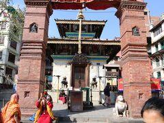 """マヘンドレシュワル寺院北の門とマヘンドレスワル寺院です。   インドラチョーク側からダルバール広場に入ると右手にある最初の寺院です。上部はネワール様式の伝統的な造りですが下部の精巧に積まれた白い石材のせいでどこか現代的な印象を受けます。  入口の門前には""""お参りセット""""を売るおばちゃん達が並んでおりなかなか活気のある寺院です。  ここにマヘンドレシュワレ寺院があり16世紀に建てれた寺院。"""