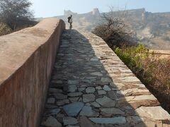 いったん坂道を降りてバスが走っている道路まで出たが、時間もあるのでジャイガル要塞まで足を延ばそうと思って、再び坂道を上ってジャイガル要塞を目指した。  前に立っているおじさんの背後にそびえたっているのが、ジャイガル要塞だ。 旧市街から見えていた山上の建造物はおそらく、ジャイガル要塞だったのだろう。