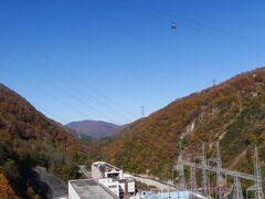 「二居湖にある奥清津発電所」  右上の上空、 これから乗る予定の田代ロープウェーが 悠々と下っていきます。  ダム湖の近くは、紅葉は終盤といった様子でした。