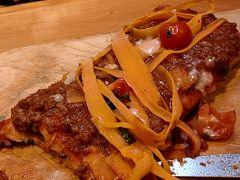 長方形のピザ生地にボロネーゼがたっぷり乗っています。 パスタのように見えるのは、ニンジンのスライスです。フォークとナイフで食べるので、ハンバーグを食べているように見えます。