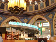 モールの建物外観はきわめて現代風ですが、内部はイスラム建築の意匠を取り入れた空間になっています。スタバの店舗は、そのモールの装飾を借景のようにしています(スタバの店舗そのものがこのデザインというわけでははく、モール全体がこのような雰囲気になっています)。  左側に写っている食べ物はドーナツなのですが・・・
