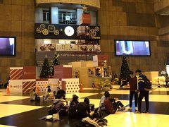 19時半過ぎ、また地下鉄で台北駅へ戻って来ました。 グランドフロアーでもクレーンを使ってクリスマスツリーを準備中。 床に座って寛いでる台北っ子たち。