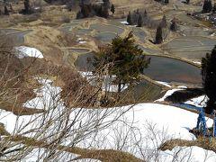雪が溶けかかっている棚田の風景。