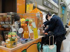 松山空港到着。 蛇口からでるみかんジュースに人が並んでます。