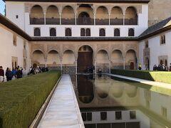 コマレスのファサードを通っていくとアルハンブラの外交および政治的活動の中心であるコマレス宮に出る。青い池が庭いっぱいに広がるアラヤネスの中庭だが、以前は外部に開かれた広場だった。写真の柱廊が建設されて南側が閉じられた。後ろに見える大きな建物がカルロス5世宮殿。