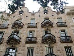 この建物は、アイシャンプル地区にある「カサ・カルベ/Casa Calvet」(1898-1900)です。 繊維業者ペレ・M・カルベの依頼により建てられたもので、1Fは所有者の事務所、2Fは所有者の居住地、3F~5Fは賃貸住宅になっていました。 現在も住居として使用されているため、中の見学は出来ません。 但し、事務所があった1Fだけは、レストラン「カサ・カルベ」となってるので食事を楽しみながら内装を楽しむことができるそうです。 残念ながら訪ねたのが早朝だったので、シャッターは開いおらず、影も形も拝めませんでした。