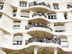 こちらは「カサ・ミラ/Casa Mila」(1905-1907)です。 実業家ペレ・ミラ夫妻のために建設された邸宅兼集合住宅で、「カサ・バトリョ」にほど近い場所に建っています。 石灰岩を主材料として使用し、建物の表面がでこぼこしている外観から「採石場」というあだ名で呼ばれました。 建物完成当時、高額な家賃(当時の一般職人の月給の約10倍)と見た目の悪さから、なかなか借り手が見つからず、家賃は3世代に渡り値上げをしないという条件で賃貸契約がなされ、現在も4世帯が実際に居住しています。