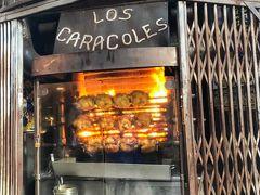 """今日こそイカスミパエリアを食べたいと思って探したレストラン""""LOS CARACOLES"""" お店の外で串刺しにした鶏をメラメラの炎で焼いている。 盗まれないのか? これは食べねば。"""